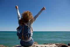 Назад молодой женщины при оружия поднятые к небу сидя водой Стоковое Изображение RF