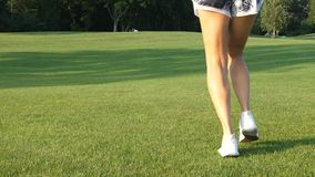 Назад ног девушки спорт бежать на луге в солнечности и ветре видеоматериал