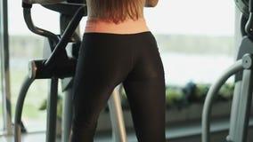 Назад худенькой тренировки женщины в эллиптическом тренере акции видеоматериалы