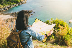 Назад девушки путешественника при рюкзак смотря направление на карте на Стоковые Изображения