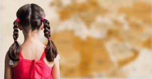 Назад девушки с оплетками против расплывчатой коричневой карты Стоковое фото RF