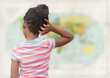 Назад девушки с рукой на голове против расплывчатой карты Стоковое Фото