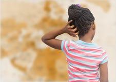 Назад девушки с рукой на голове против расплывчатой коричневой карты Стоковая Фотография RF