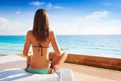 Назад женщины сидя в положении йоги около моря Стоковые Фотографии RF