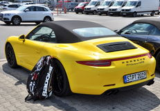Назад желтого Порше 911 Carrera 4 GTS с сумкой Babolat тенниса Стоковое фото RF