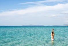 Назад красивой женщины нося голубое бикини стоя в воде на побережье Средиземного моря, Cesme, пляж Ilica, Турция Стоковые Фотографии RF
