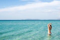 Назад красивой женщины нося голубое бикини стоя в воде на побережье Средиземного моря, Cesme, пляж Ilica, Турция Стоковая Фотография