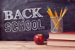 Назад к литерности школы с книгами, карандашами и яблоком над предпосылкой доски