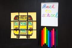 Назад к предпосылке школы с ` названия назад к ` ` школы и школьного автобуса ` написанному на желтых кусках бумаги, тетрадь с на Стоковые Изображения RF