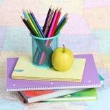 Назад к принципиальной схеме школы. Яблоко и покрашенные карандаши на куче книг над картой Стоковая Фотография