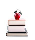 Назад к школе: Будильник Яблока на стоге книг Стоковое Фото