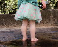 Назад малыша стоя barefoot в лужице Стоковые Фотографии RF