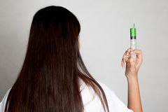 Назад молодого азиатского женского доктора с шприцем Стоковое Изображение