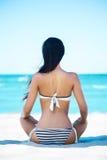 Назад молодой женщины ослабляя на пляже Стоковые Фото