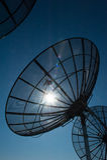 Назад освещенное солнце спутниковых антенна-тарелок радиосвязи Стоковые Изображения RF