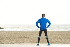 Назад человека спорта смотря на море Стоковое Изображение