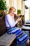 Назначьте встречуа Сторона женщины восторженная с smartphone создает назначение в социальной сети и ждет кафе друзей стоковые изображения rf