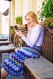 Назначьте встречуа Сторона женщины восторженная с smartphone создает назначение в социальной сети и ждет кафе друзей стоковая фотография
