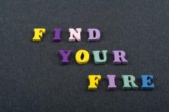 НАЙДИТЕ ВАШЕ слово ОГНЯ на черной предпосылке доски составленной от писем красочного блока алфавита abc деревянных, скопируйте ко Стоковые Изображения RF