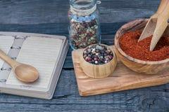 Накаленный докрасна перец chili и перчинка и рецепт записывают на темной деревянной предпосылке Стоковые Фото