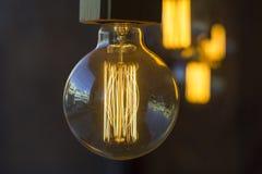 Накаляя вися сферически ретро винтажные лампочки накаливания edison против запачканной темной стены и других ламп стоковая фотография rf