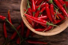 Накаленные докрасна перцы chili в деревянном шаре на деревянной предпосылке пряно стоковые изображения rf