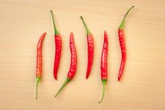 Накаленные докрасна перцы chili на деревянном столе Стоковая Фотография