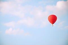 Накаленный докрасна воздушный шар в голубом небе с белыми облаками Стоковое Изображение