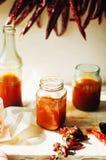 Накаленный докрасна сладостный соус чилей над старой белой деревянной предпосылкой Русь Стоковая Фотография