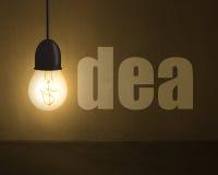 Накаляя лампа с символом денег и словом идеи на бетонной стене внутри Стоковая Фотография
