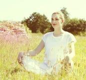 Накаляя молодая женщина йоги предусматривая размышлять, солнечные ретро влияния Стоковая Фотография RF