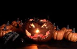 Накаляя страшные украшения и рука тыквы в темной предпосылке стоковая фотография rf