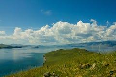 Накидка с зеленой травой и голубым озером Стоковая Фотография