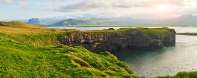Накидка Dyrholaey на южной Исландии Высота 120 m, и средний остров холма с отверстием двери Стоковое Изображение