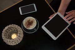 Накладные расходы женщины используя цифровую таблетку пока имеющ кофе Стоковые Фото