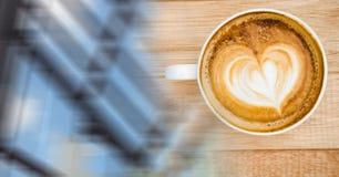 Накладные расходы кофейной чашки с формой сердца в пене и расплывчатое окно переводят Стоковые Фото
