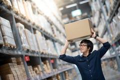 Накладные расходы нося картонной коробки молодого азиатского человека в складе Стоковые Фотографии RF