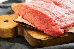 Накладные расходы стейков говядины на деревянной разделочной доске Куски говядины Стоковое фото RF