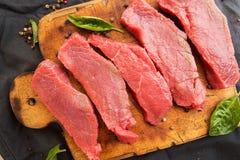 Накладные расходы стейков говядины на деревянной разделочной доске Куски говядины Стоковое Изображение