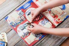 Наклеивать стикеры Panini в альбом для чемпионата 2018 Стоковое Изображение