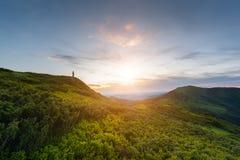 Наклоны зеленого лета высокогорные на заход солнца с силуэтом человека, предпосылки перемещения природы, прикарпатских гор Стоковые Фотографии RF