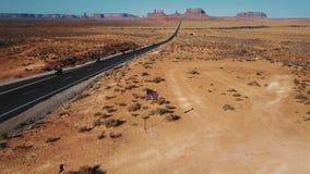 Наклоны камеры трутня до показывают американский флаг развевая в середине долины памятника, велосипедистов проходя мимо на дорогу