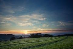 Накошенное поле в заходе солнца Стоковые Фото