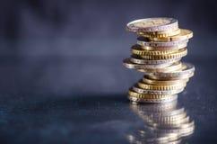 накрените веревочка примечания дег фокуса 100 евро 5 евро Монетки изолированы на темной предпосылке с отражением в стекле Валюта  Стоковое Изображение RF