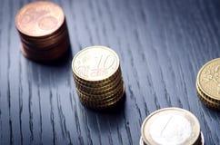 накрените веревочка примечания дег фокуса 100 евро 5 евро Монетки на темной предпосылке Валюта Европы Баланс денег Здание от моне Стоковые Изображения RF