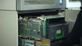 Накрените работник раскрывая сейф ATM, принимая вне пачку долларов, наличн-в-переход акции видеоматериалы
