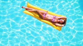 Накладные расходы брюнет лежа на lilo в бассейне на солнечный день сток-видео