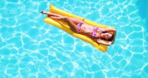Накладные расходы брюнет лежа на lilo в бассейне на солнечный день видеоматериал