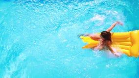 Накладные расходы брюнет сидя на lilo в бассейне на солнечный день видеоматериал