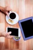 Накладные расходы женственных рук держа smartphone и кофе Стоковая Фотография